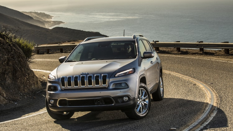 2015 Jeep Cherokee Limited in silver on a winding oceanside road