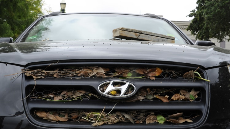 An abandoned vehicle is covered in flood debris in downtown Houston