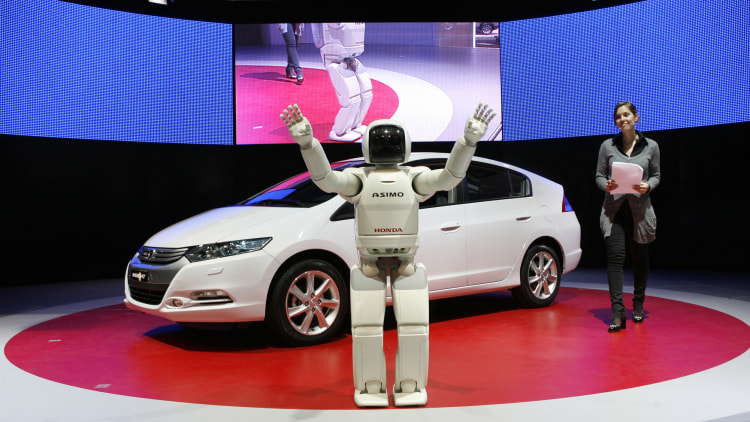 Honda's Asimo robot waves in front of a Honda Insight hybrid
