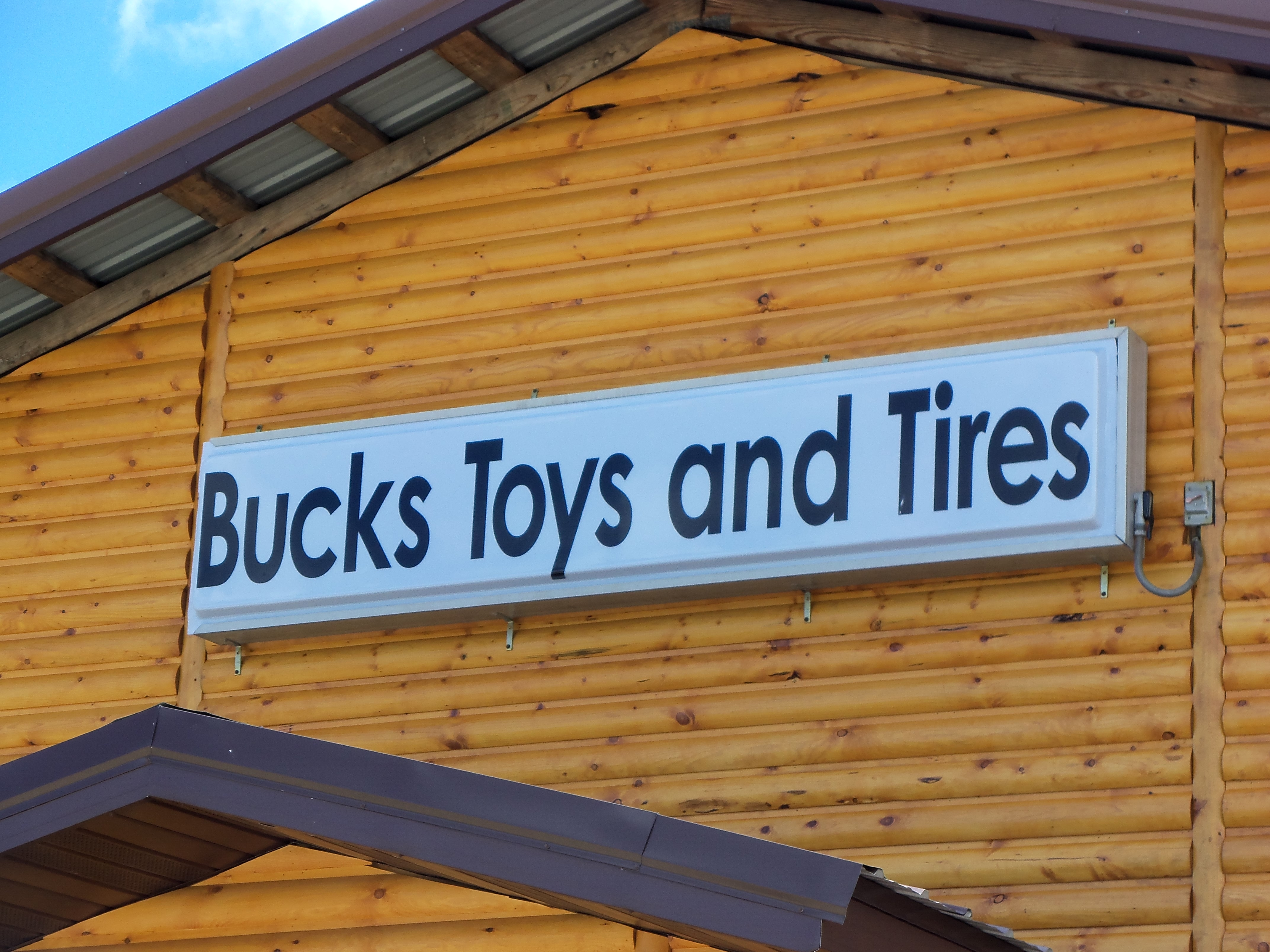 Log Sided Building - set back from Hwy 65. Bucks Toys and Tires