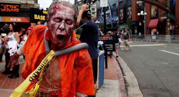 SAN DIEGO, CA - JULY 19:  A zombie character greets people along 5th Avenue in the Gaslamp Quarter at Comic Con on July 19, 2013 in San Diego, California.  Comic Con International Convention is the world's largest comic and entertainment event and hosts celebrity movie panels, a trade floor with comic book, science fiction and action film-related booths, as well as artist workshops and movie premieres. (Photo by Sandy Huffaker/Getty Images)