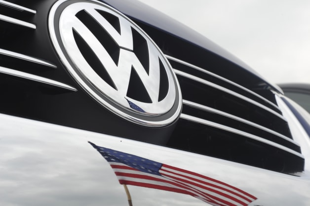 The American flag is reflected in the bumper of a new VW