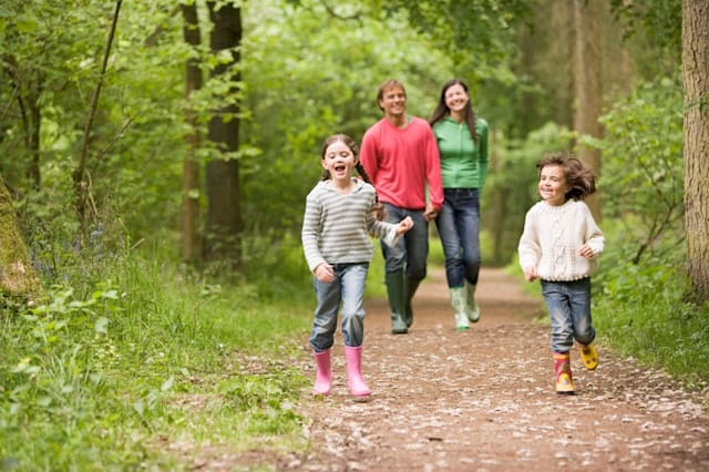 B3FAW1 Family walking on path holding hands smiling