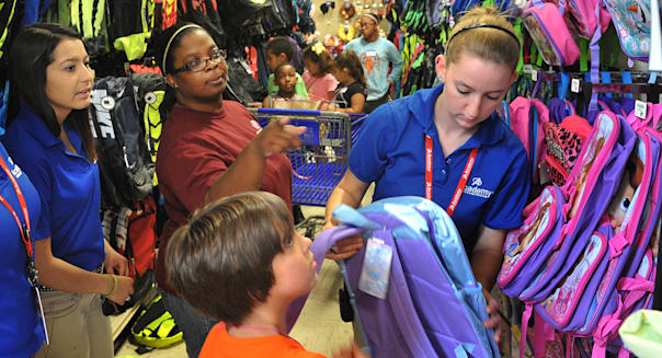 FILE - In this Wednesday, Aug. 5, 2015, file photo, Tori Smith, center, director of the Southwest Branch of the Boys and Girls Club in Wichita Falls, Texas, and employees of Academy Sports and Outdoors help several club members pick out new backpacks for school. To get the best back-to-school deals, experts say it's all in the timing. (Torin Halsey/Wichita Falls Times Record News via AP, File)