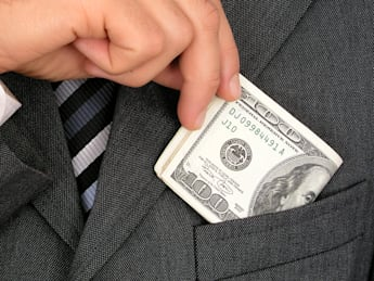 businessman putting money into...