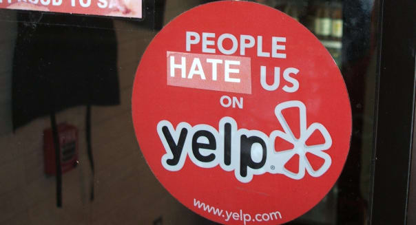 A Yelp sticker. The review site has come under fire by small businesses who question its business practices.