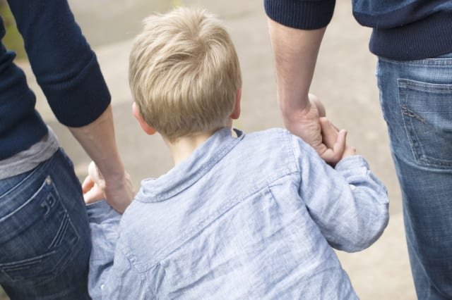 Little boy holding parents hands