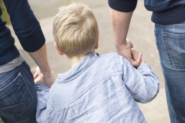 Little boy holding parents hands