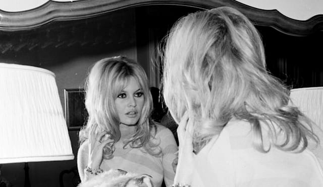 Brigitte Bardot checks her appearance in mirror at the Plaza