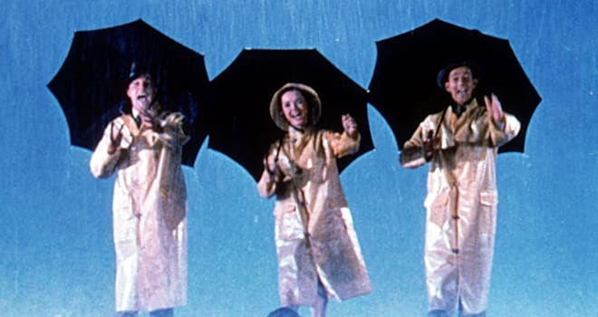 "Full shot of illustration of Gene Kelly as Don Lockwood, Debbie Reynolds as Kathy Selden, and Donald O'Connor as Cosmo Brown walking together in rain, holding umbrellas during the opening musical number ""Singin' In The Rain."""