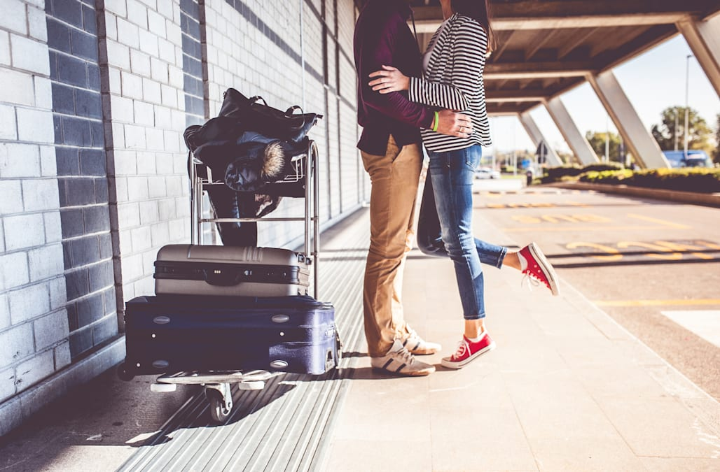 Young couple kissing outside airport
