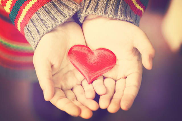 closeup of a girl's hands holding a red silky heart