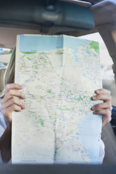 Couple travelling by car, man driving, woman reading map