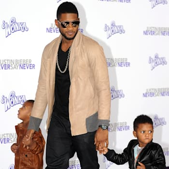 Singer Usher arrives with his children at the premiere of 'Justin Bieber: Never say Never in Los Angeles, California on February 8, 2011. AFP PHOTO / GABRIEL BOUYS (Photo credit should read GABRIEL BOUYS/AFP/Getty Images)