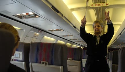 DENVER COLO, MAR 09, 2006--United Airlines flight attendent, Kathy<CQ> O'Connor<CQ>, points to the other near by exits, Thursday