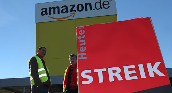 Employees of  American online retailer Amazon demonstrate during a strike in front of the logistics center, in Graben,  near Augsburg, Germany,  Monday, Dec. 16, 2013.   Hundreds of workers at Amazon.com in Germany have walked off the job in an effort to put pressure on the American online retailer in the busy days before Christmas to settle on a new wage agreement. The ver.di union said Monday that several hundred workers were staging one-day warning strikes at Amazon logistics centers in Leipzig, Bad Hersfeld and Graben.  Word on poster at right reads : Strike. (AP Photo/dpa, Karl-Josef Hildenbrand)