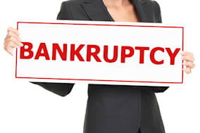Bankruptcy sign being held by woman in business suit