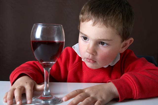 Four year old boy with red wine