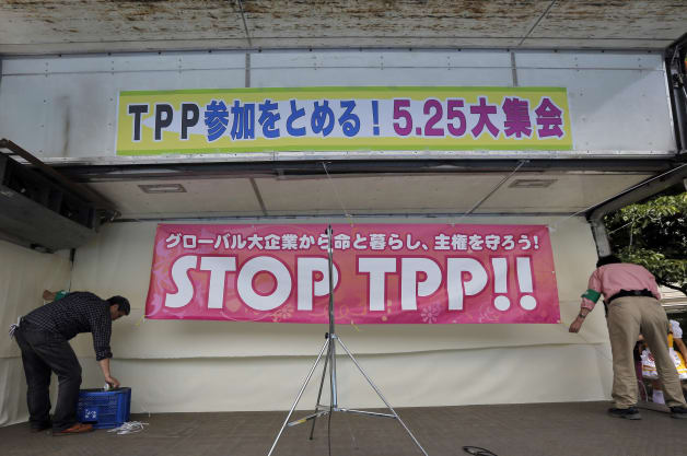 Protesters prepare a banner at a stage before the start of a rally against the Trans-Pacific Partnership (TPP)in Tokyo, Saturday, May 25, 2013. U.S. and Japan earlier agreed on robust actions in the automotive and insurance sectors, as well as other non-tariff measures _ key areas of U.S. concern. But they will need to hold further negotiations in parallel with the TPP talks to further iron out their differences. The banner, top, reads: