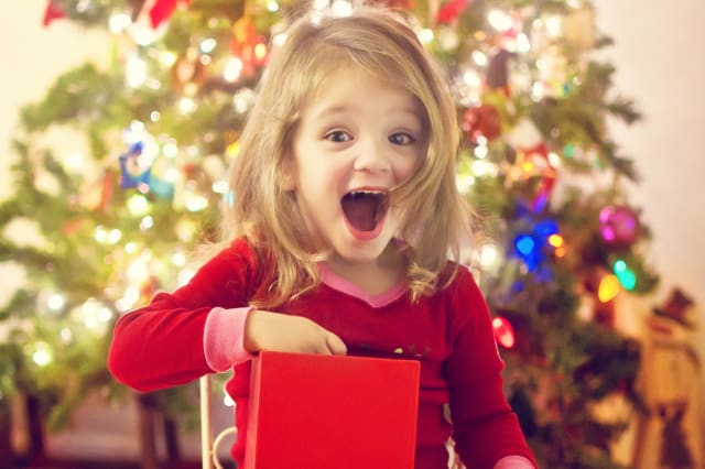 Girl surprised after opening Christmas gift