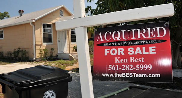 A Acquired Realty & Investments Inc. for sale sign hangs in front of a foreclosed home in Lake Worth, Florida, U.S., on Wednesday, March 30, 2011. Letting homeowners unload properties for less than their mortgage debt may stem home-price declines by preventing foreclosures, which drag down overall values by selling at discounts. The problem is short sales are rising at about half the pace of home seizures as a lengthy consent process by loan holders deters potential buyers. Photographer: Mark Elias/Bloomberg via Getty Images