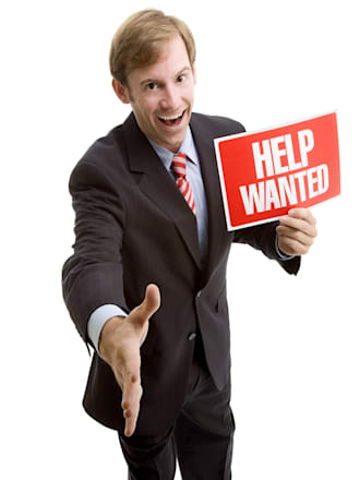 A handsome young businessman stands holding a Help Wanted sign with his hand outstretched for a handshake.