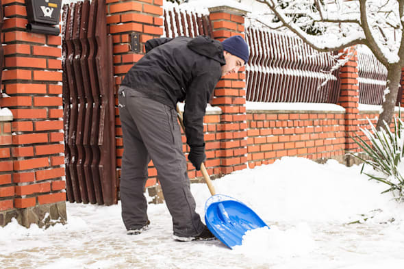 young man remove snow near the...