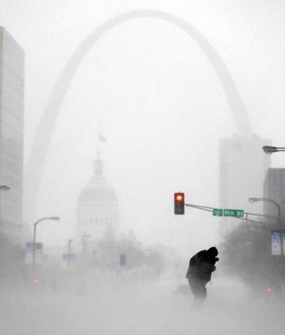 ... snow as the Gateway Arch appears in the distance, in St. Louis, Mo