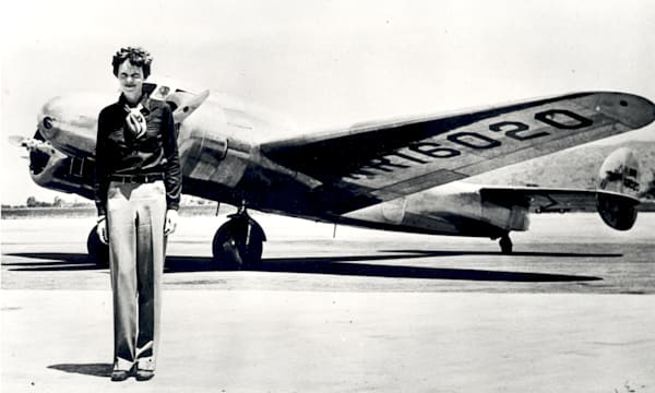 Amelia Earhart standing in front of the Lockheed Electra in which she disappeared in July 1937. Born in Atchison, Kansas in 1897