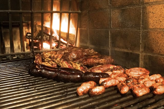 Argentinian barbacue, including all meat and sausages typical form latin america, with fire at the back