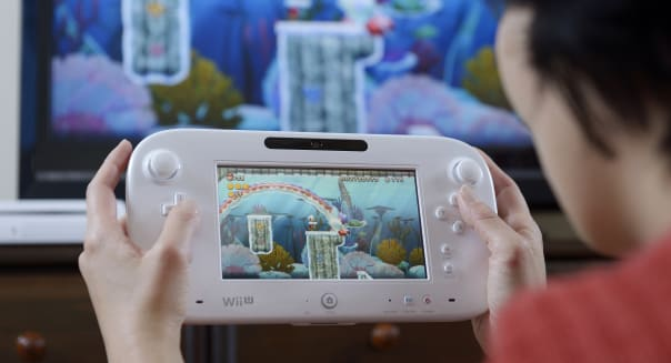 A woman holds a Nintendo Co. Wii U touch-screen controller displaying the new Super Mario Bros. U game in this arranged photograph in Kawasaki City, Kanagawa Prefecture, Japan, on Tuesday, Jan. 29, 2013. Sony Corp. and Nintendo Co., Japan?s biggest makers of gaming devices, rose after China Daily said the world?s most-populous country may end a 12-year ban on the sale of video-game consoles. Nintendo, the creator of Super Mario, added 3.4 percent to 9,630 yen, the highest since Dec. 7, in Osaka. Photographer: Akio Kon/Bloomberg via Getty Images