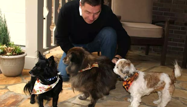 In this Nov. 23, 2014 photo provided by Jan Trantham, Will Trantham kneels by Jackson, left, a Shih Tzu, along with Darcy, center, and Sophie. Trantham and his wife adopted Jackson when they checked into Aloft Hotel in downtown Asheville, N.C., that is believed to be the only hotel in the United States where guests can adopt the front desk dog. (AP Photo/Jan Trantham)