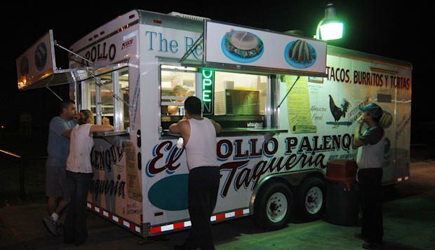 Patrons gather around the Pollo Palenque taco truck in the p