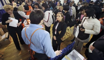 Job seekers crowd around a Home Depot booth during the Caree