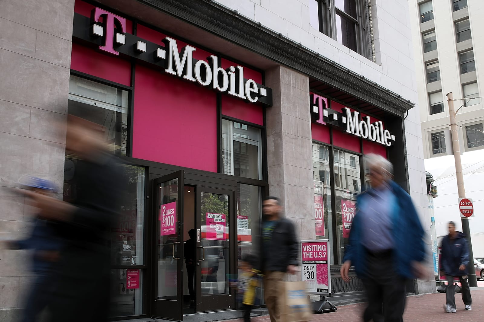 pedestrians-walk-by-a-tmobile-store-on-a