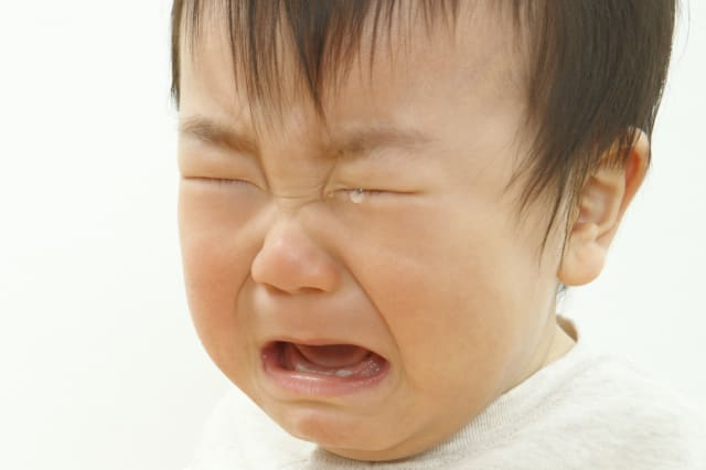 Close-up of a baby boy crying against white background