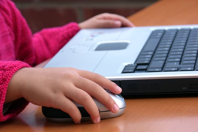 Little girl learning how to use computer to surf the Internet.