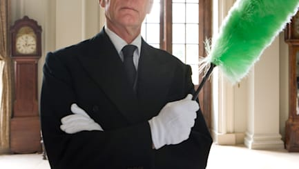 B0BJTX Butler with duster, arms crossed, portrait  butler; arms; crossed; color; image; horizontal; indoors; photography; caucas