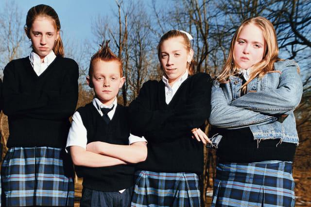 Five schoolchildren (8-13) standing with arms crossed, portrait