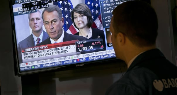 Wall Street Budget Battle (Specialist Frank Masiello watches a television monitor on the floor of the New York Stock Exchange sh