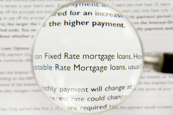 B5JD2X A magnifying glass highlights fixed interest rate and adjustable interest rate mortgage loans as part of a real estate co