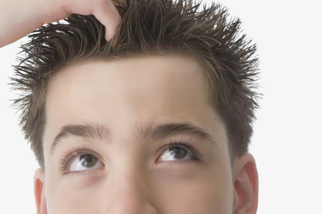 Hispanic boy with hand in hair
