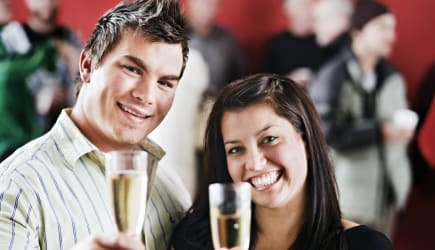 Good looking couple raise glasses in toast at a party