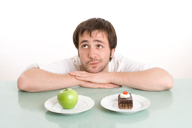 Green apple and chocolate cake on dishes. Young man is thinking what he will eat.