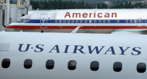 FILE - This Tuesday, Aug. 13, 2013 file photo shows an American Airlines plane and a US Airways plane at parked at Washington's Ronald Reagan National Airport. On Tuesday, Nov. 12, 2013, the Justice Department says it has reached an agreement to allow the merger of the two airlines. The agreement requires them to scale back the size of the merger at key airports in Washington and other big cities. (AP Photo/Susan Walsh)