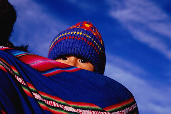 Bolivia, La Paz, young child wrapped in cloth on mother's back
