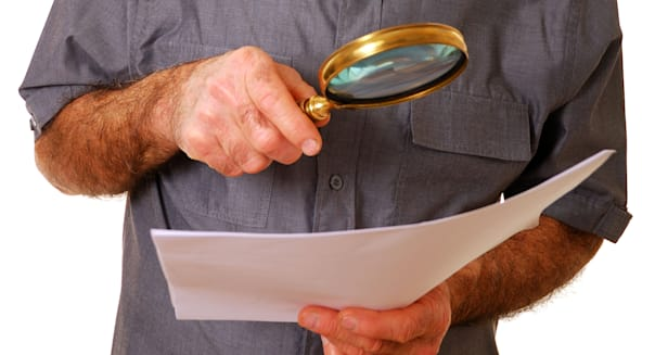 Elderly man using magnifying glass to read