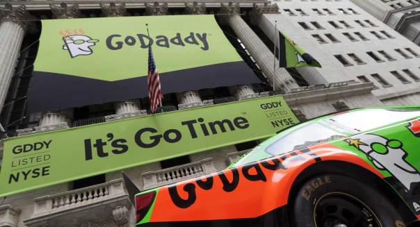 GoDaddy signage and Danica Patrick's race car announce the company's IPO, in front of the New York Stock Exchange, Wednesday, April 1, 2015. (AP Photo/Richard Drew)