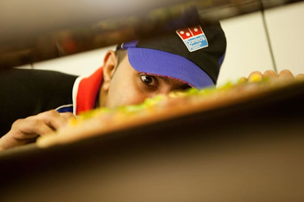 Domino's Pizza employee looks in pizza oven