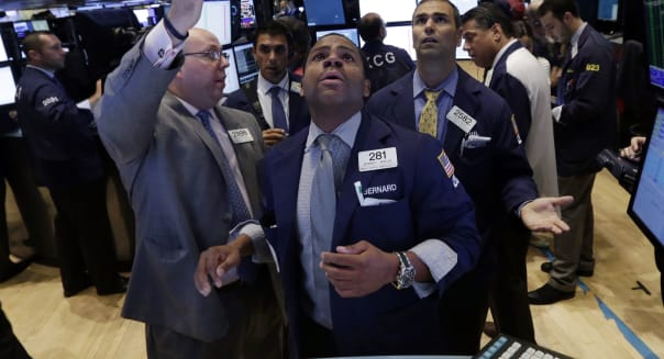 Specialists Peter Kennedy, Bernard Wheeler, and Philip Finale, left to right, confer on the floor of the New York Stock Exchange Wednesday, July 31, 2013. Steady growth in the U.S. economy and higher company earnings are pushing the stock market higher in early trading. (AP Photo/Richard Drew)